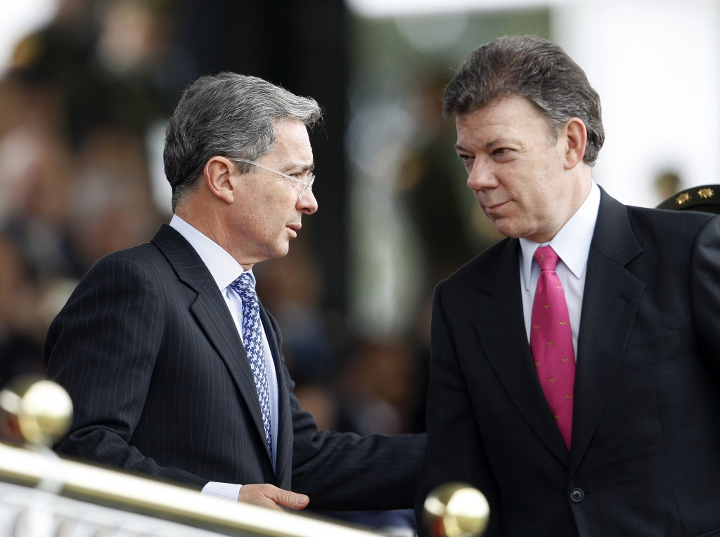 Colombian President Uribe speaks with Defense Minister Santos during an army ceremony at Police School in Bogota